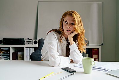 Young woman with cup of coffee at desk in office - p300m1537282 by Michael Bader