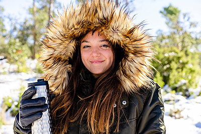 Smiling woman wearing fur hooded winter coat holding bottle while standing at forest - p300m2250946 by Javier De La Torre Sebastian