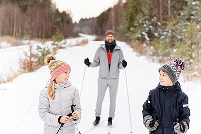 Father with children skiing on snowy landscape in forest - p300m2251201 by Ekaterina Yakunina