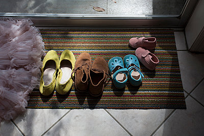 Different size shoes lined up on doormat - p924m1197272 by Kinzie Riehm