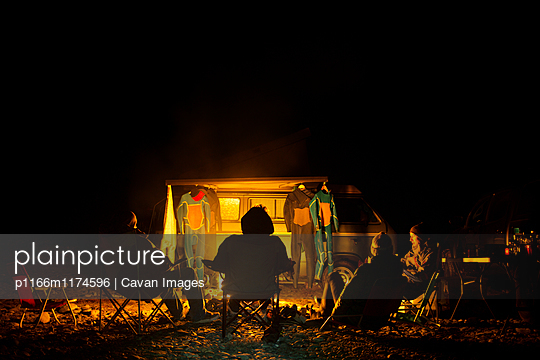 Friends camping while relaxing on chair at beach - p1166m1174596 by Cavan Images