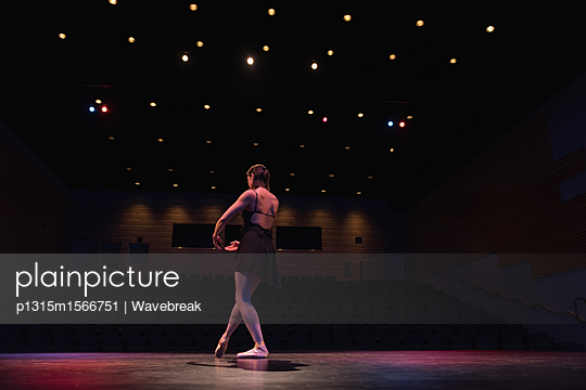 Ballet dancer dancing on stage at theatre - p1315m1566751 by Wavebreak