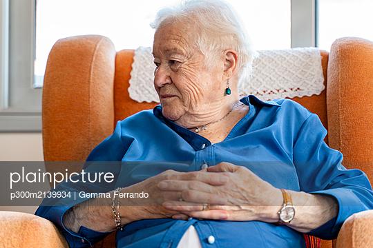Elderly woman sitting in an armchair in living room - p300m2139934 by Gemma Ferrando