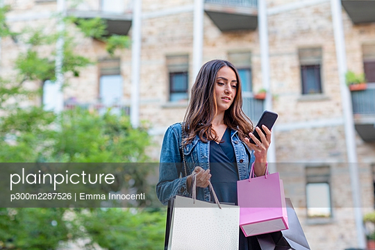 Young woman with jeans jacket and shopping bags outdoor looking at phone; Florence, Italy - p300m2287526 von Emma Innocenti