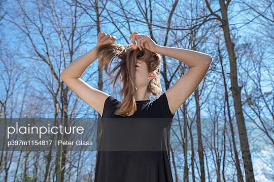 Weiblicher Teenager steht vor Bäumen - p397m1154817 von Peter Glass