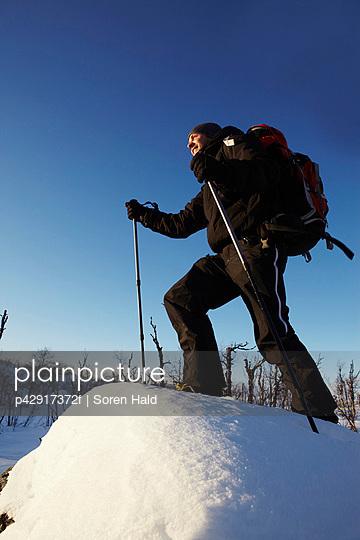 Cross-country skier walking in snow