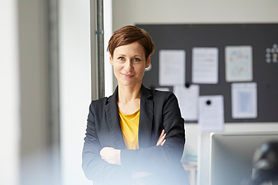 Attractive businesswoman standing in office with arms crossed - p300m2012999 von Rainer Berg