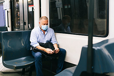 Businessman in face mask using smart phone while traveling in train - p300m2206546 by Daniel González