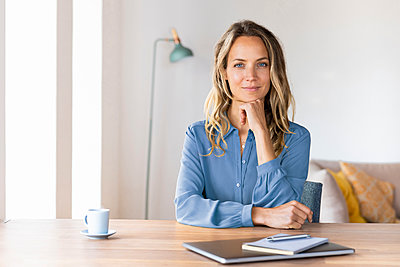 Beautiful businesswoman with hand on chin sitting at desk in home office - p300m2276384 by Steve Brookland