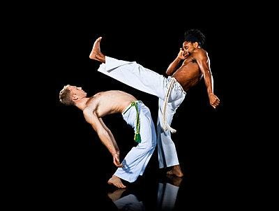 Two men practising capoeira, one kicking out and the other bending backwards - p924m742139 by Rivers Dale