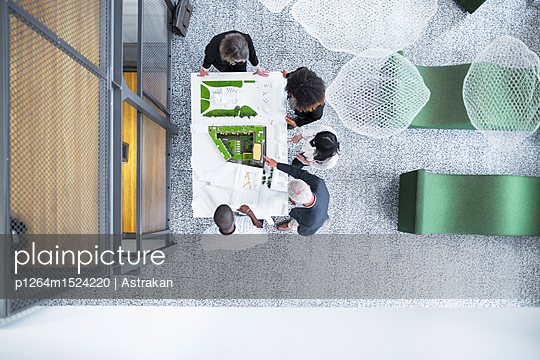 Overhead view of architects discussing blueprint - p1264m1524220 by Astrakan