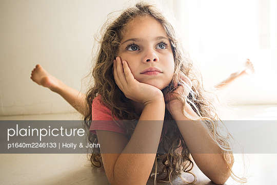 Little girl with curly hair day dreaming - p1640m2246133 by Holly & John