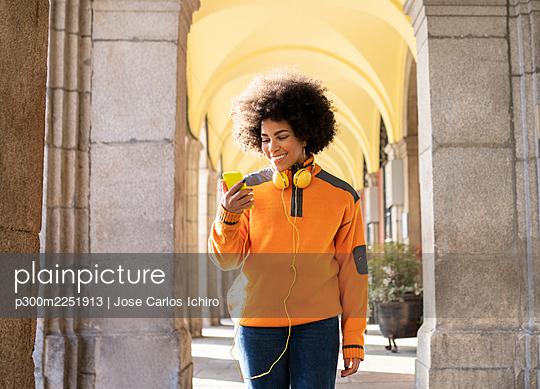 Smiling young woman using mobile phone while walking at corridor - p300m2251913 by Jose Carlos Ichiro