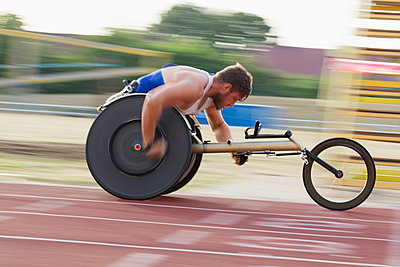 Determined young male paraplegic speeding on sports track in wheelchair race - p1023m2067562 by Martin Barraud