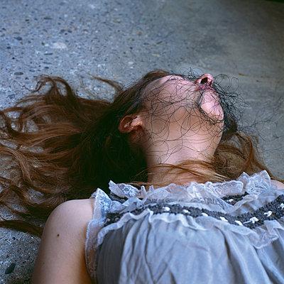 Tote junge Frau mit Faden im Gesicht - p1550m2128399 von Kumi Oguro