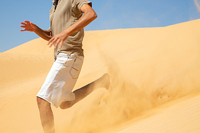 Man Running Down A Dune - p1655m2288472 by lindsay basson