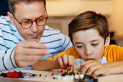 Father and son assembling an electronic construction kit - p300m1562324 by Bonninstudio