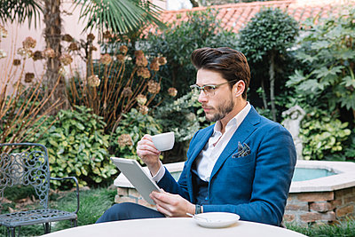 Elegant businessman using tablet in a garden cafe - p300m2012406 von Alberto Bogo