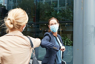 Businesswoman and colleague with face mask greeting with elbow bump while standing against office building - p300m2227074 by Pete Muller