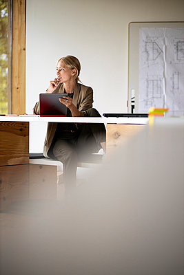 Thoughtful businesswoman using digital tablet while sitting by tablet at home - p300m2241482 by Peter Scholl