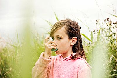 Girl (5-7) using asthma inhaler, Southwold, Suffolk, United Kingdom - p300m2298745 von LOUIS CHRISTIAN