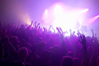 Rays of purple spotlights over crowded dance floor at nightclub - p426m766299f by Helena Wahlman