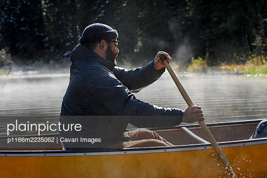 Close up of bearded man paddling canoe on a foggy lake in Canada - p1166m2235062 by Cavan Images