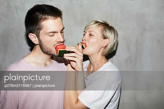 Couple feeding a melon  - p276m2115567 by plainpicture