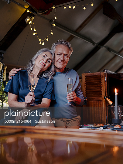 Portrait of senior couple having a candlelight dinner on a boat in boathouse - p300m2154964 by Gustafsson