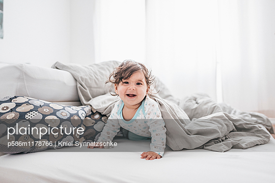 Toddler girl playing on bed - p586m1178766 by Kniel Synnatzschke