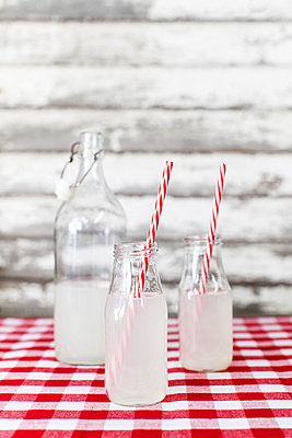 Lemonade bottles with striped straw on tablecloth - p1094m1015330 by Patrick Strattner