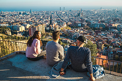 Spain, Barcelona, three friends sitting on a wall overlooking the city - p300m1562205 by VITTA GALLERY