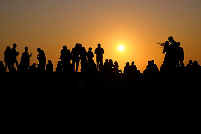 Portugal, Algarve, Silhouettes of people relaxing against setting sun at Cape Saint Vincent - p300m2144193 by Michael Reusse (alt)