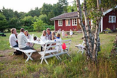 Family having meal in garden, oland, Sweden - p312m927337f by Lena Granefelt