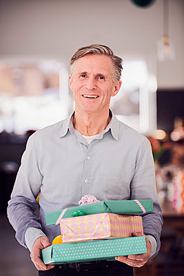 Portrait of senior man holding stacked gift boxes while standing at home - p426m1580237 by Maskot