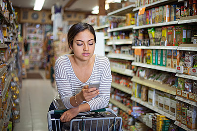 Young woman shopping with smartphone in health food store - p924m1012430f by Raphye Alexius