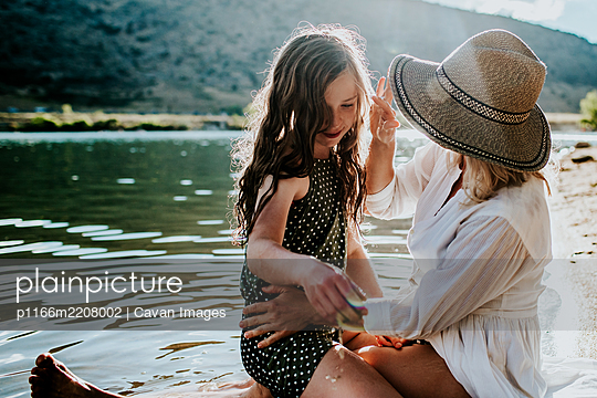 Mother and daughter sitting on lake shore having a quiet moment - p1166m2208002 by Cavan Images