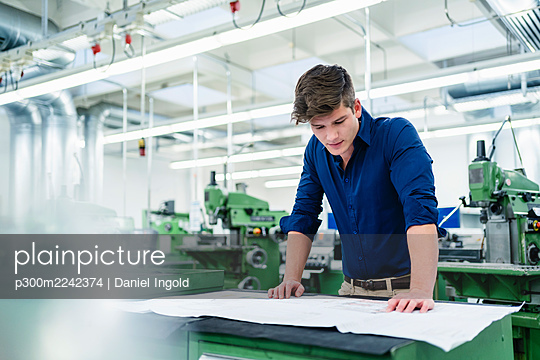 Male entrepreneur looking over floor plan while working on desk in factory - p300m2242374 by Daniel Ingold