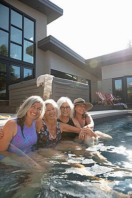Portrait happy, affectionate, carefree senior women friends swimming in sunny, summer swimming pool - p1192m2129517 by Hero Images