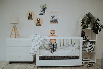 Baby standing in cot - p1414m2044862 by Dasha Pears