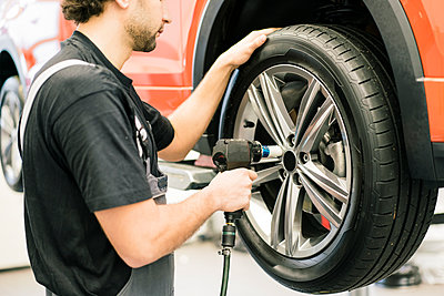Car mechanic in a workshop changing tire - p300m2166810 by Robijn Page