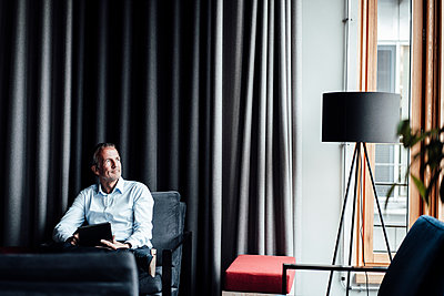Thoughtful male entrepreneur with digital tablet looking away while sitting on armchair in cafeteria at office - p300m2265750 by Gustafsson