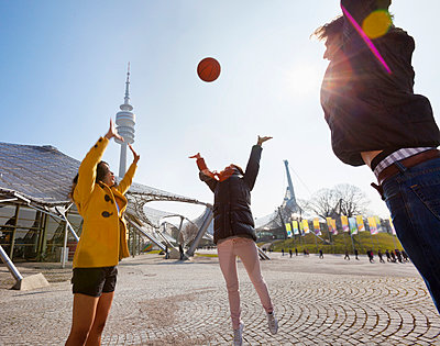 Germany, Bavaria, Munich, Three friends playing basketball at the Olympic Park - p300m979995 by hsimages