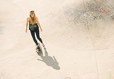 High angle of young female skateboarder skateboarding in skatepark - p429m1188215 by Ben Pipe Photography