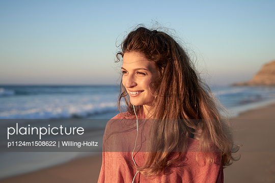Young woman with earphones on the beach - p1124m1508622 by Willing-Holtz
