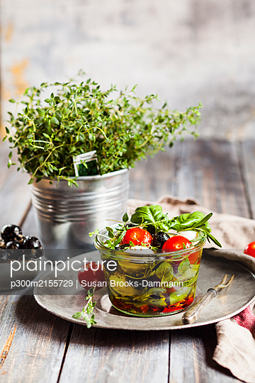 Potted thyme and jar of freshCapresesalad preserved in olive oil - p300m2155729 by Susan Brooks-Dammann