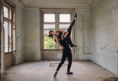 Man lifting ballerina while practicing ballet in old building - p1166m2024698 by Cavan Images