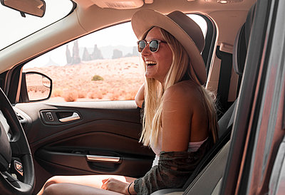 Side view of happy woman wearing hat and sunglasses while traveling in car at Monument Valley Tribal Park - p1166m2025128 by Cavan Images