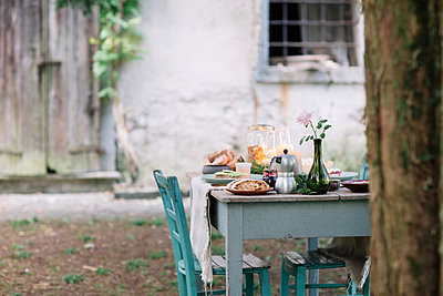 Laid garden table with candles next to a cottage - p300m2068442 by Alberto Bogo