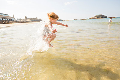 Caucasian girl splashing in waves on beach - p555m1410491 by Mike Kemp
